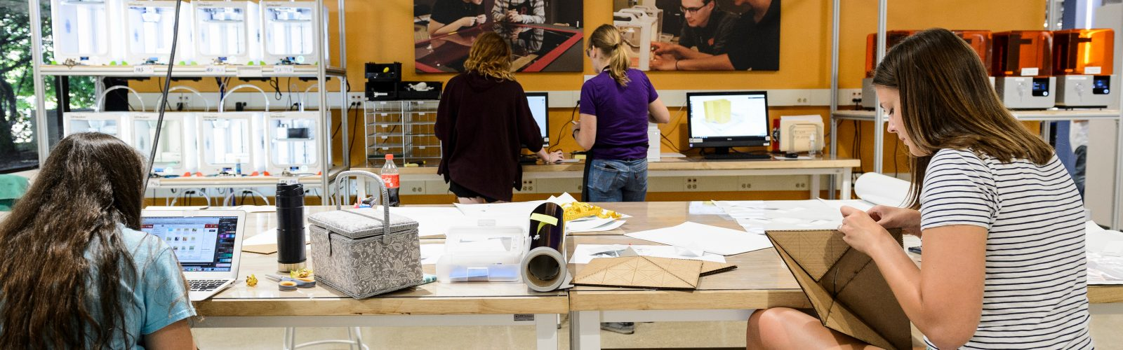 Photo of makerspace with yellow wall and students working